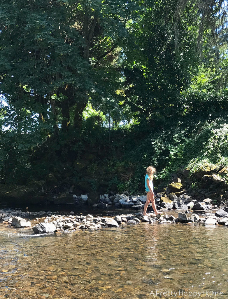 girl playing in creek finding natural rock soap dish