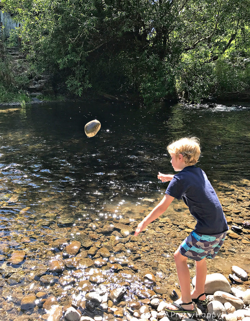 boy throwing rock in creek finding natural rock soap dish