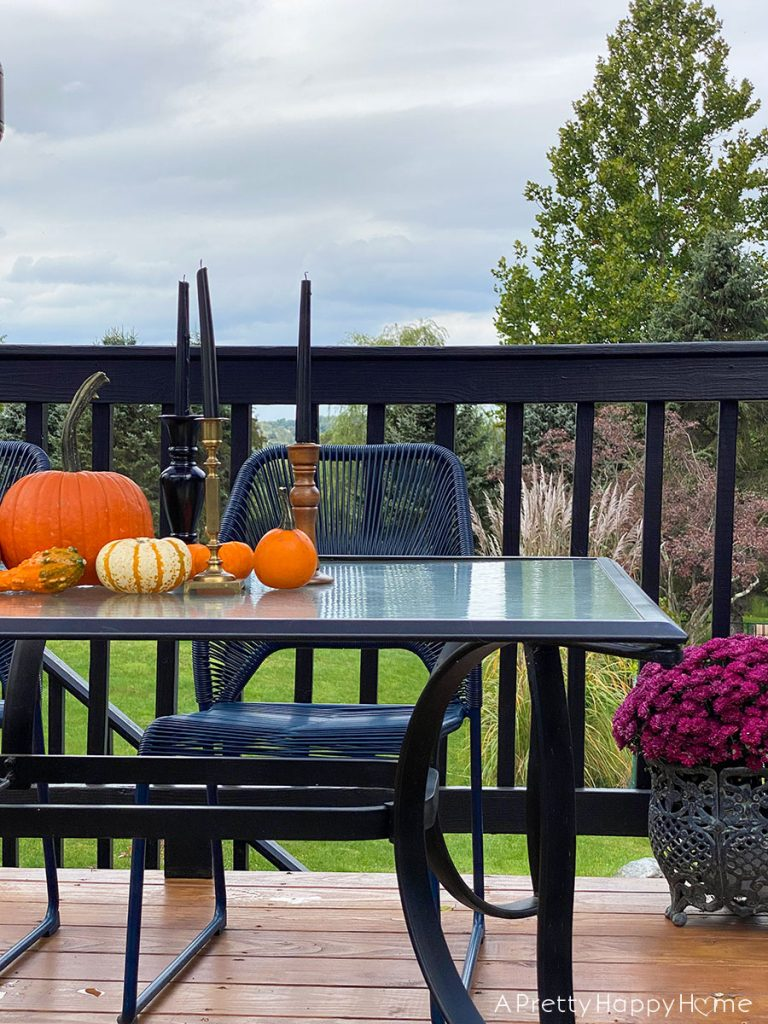 colonial farmhouse deck in fall black and blue outdoor furniture