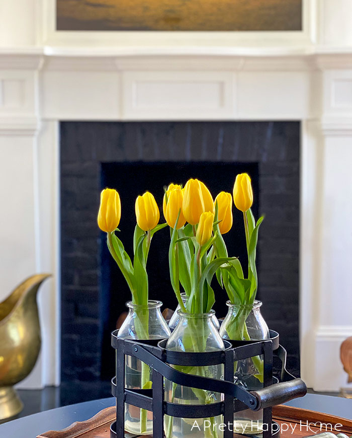 yellow tulips in milk bottle on the happy list